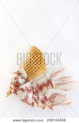 empty wafer cone in warm pink scarf on a light surface top view / capacity for your winter ice cream