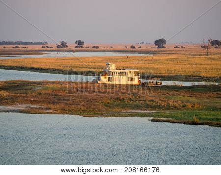 Large houseboat laying on Namibian side of bank of Chobe River in Chobe National Park, Botswana, Southern Africa.