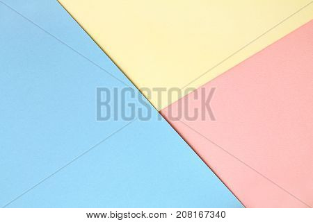 Abstract asymmetrical geometric watercolor paper background in three colors soft pastel pink blue and yellow trend colors.