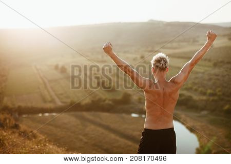 Back view of muscular man standing on the top of mountain with hands up.
