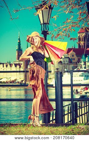 Spending money on sales buying things concept. Fashionable woman relaxing and standing with shopping bags in town wearing windblown long dress and sun hat