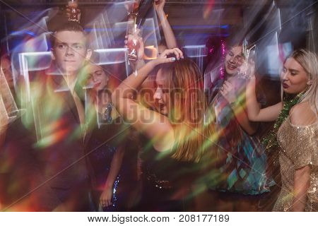 Dancing at night club in blurred motion. Joyful friends at Christmas discotheque, active New Year company with drinks, modern youth life