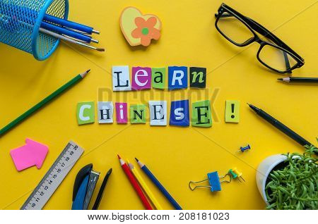Word LEARN CHINESE made with carved letters on yellow desk with office or school supplies, stationery. Concept of chinese language courses.