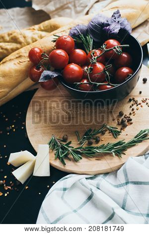 Tasty fresh tomatoes in a stylis black dish with delicious bread lying on wooden cutting board ready for cooking and making amazing meal for lunch or dinner. Yammi