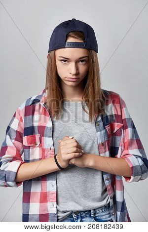 Angry teen girl wearing checkered shirt and baseball cap over grey background looking at camera sullen and clenching her fists , front view