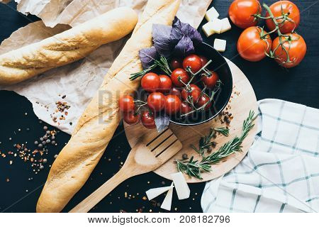 Tasty fresh tomatoes in a stylis black dish with delicious bread lying on wooden cutting board ready for cooking and making amazing meal for lunch or dinner.