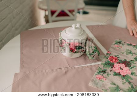 white kettle wrapped in a scarf on the table