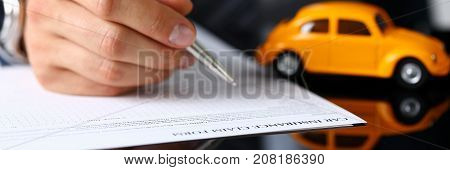 Male arm in suit filling insurance form lying on table with silver pen closeup. Strike a bargain, driver money loss prevention, secure road trip, harmless drive idea, owner protective offer concept