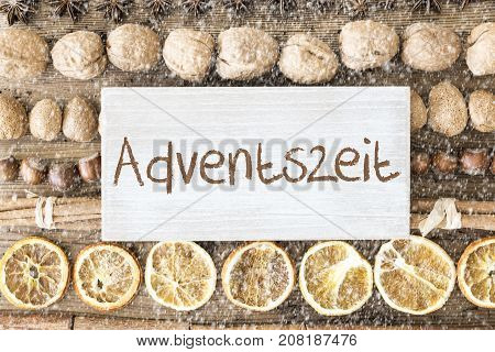 Sign With German Text Adventszeit Means Advent Season. Christmas Food Flat Lay With Walnut, Hazelnut, Cinnamon Sticks And Orange Peel. Brown Wooden Background With Snowflakes