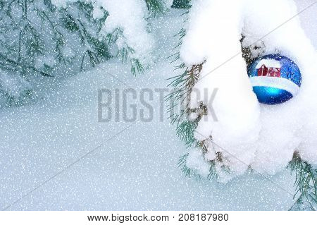 Christmas toy on a snowy branch in the forest. Christmas fabulous composition