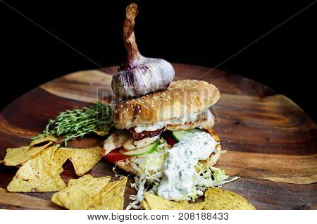 Creatively styled beef burger with rustic home-made French chips or crisps shot against a dark background with generous accommodation for copy space. garlic on top