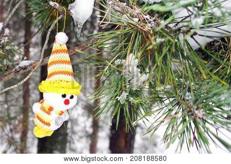 Snowman on a branch in winter forest. Fairytale Christmas composition