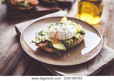 Sandwich with avocado and poached egg .
