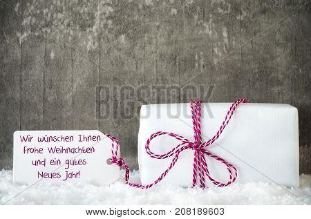One White Gift With Label With German Text Wir Wuenschen Ihnen Frohe Weihnachten Und Ein Gutes Neues Jahr Means We Wihs You A Merry Christmas And A Happy New Year. Cement Background With Snow.