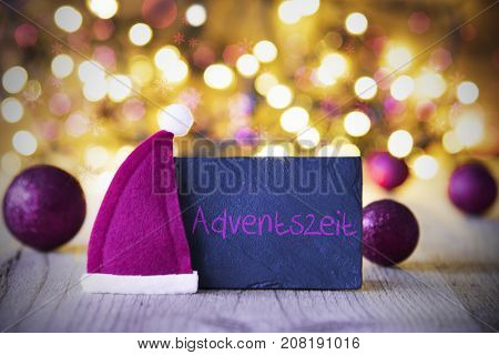 Plate With German Text Adventeszei Means Advent Season. Purple Christmas Ball Ornaments And Santa Claus Hat. Wooden Background With Lights