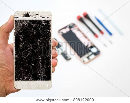 Close-up of cracked smartphone screen in technician hand on blurred smartphone component background with copy space