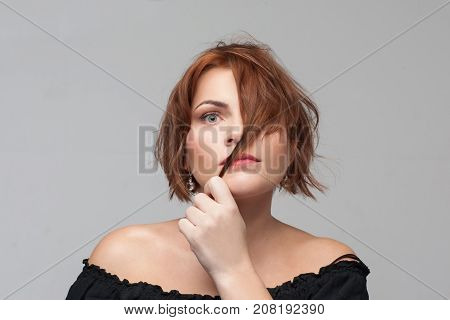 Ashamed of appearance. Hair problems. Shy young woman portrait on grey background with free space, introvert person