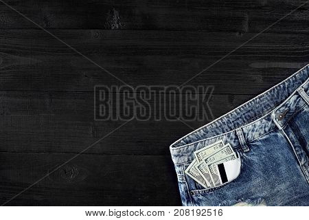 Cash and cards in your pocket jeans on black wooden background. Top view. Copy space. Still life. Flat lay