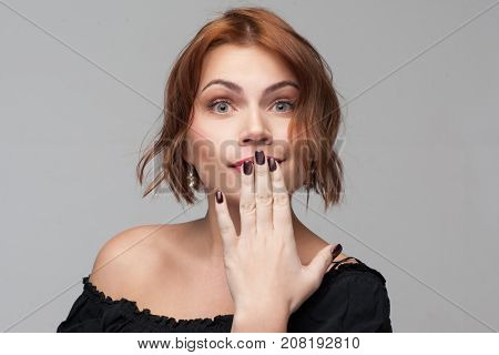 Female secrets. Flirty confusion young woman. Surprising news, shocked facial expression. Playful girl portrait on grey background, gossip concept