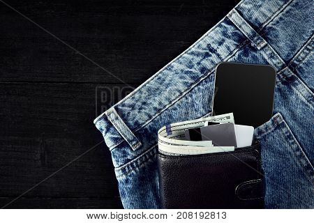 Money, Smart, Debit card and Credit card are in pocket of blue jean on wooden background with copy space. One hundred dollar bills and cards in back of jean pocket in concept of business and finance.