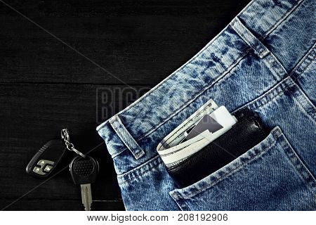 Money, Debit card and Credit card are in pocket of blue jean, Car keys on wooden background with copy space. One hundred dollar bills and cards in back of jean pocket in concept of business