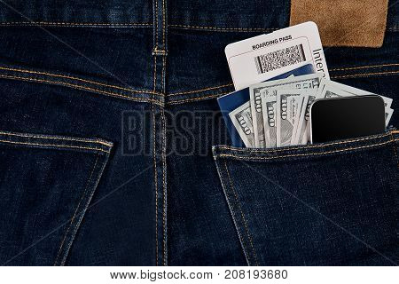 Dollars, smart, passport and plane ticket in your pocket jeans. Top view. Copy space. Still life. Flat lay