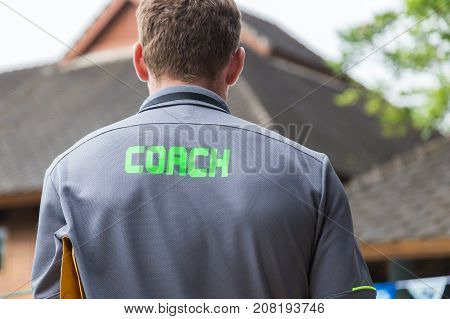 back of a male coach's grey shirt with the green word Coach written on it compose to leave space on left side for text or graphics good background for sport or coaching theme
