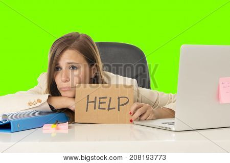 young attractive sad and desperate businesswoman suffering stress at office laptop computer desk holding help sign depressed in business problem isolated on green screen chroma croma key background