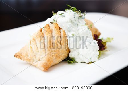 Traditional russian pie - coulibiac. Baked puff pastry filled with smoked salmon, served with sour cream sauce