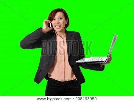 Happy business woman with red hair talking on the mobile cell phone holding laptop in hand isolated on green screen chroma croma key or cromakey background for composite