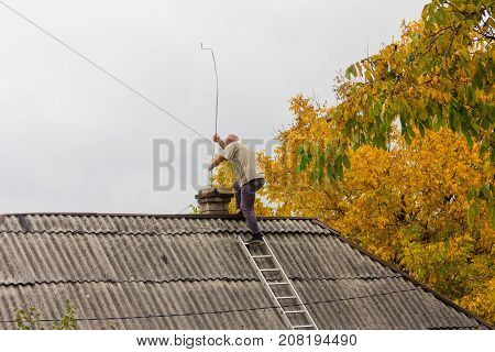male chimney sweep cleans the chimney on the roof of a village house the preparation for the heating season