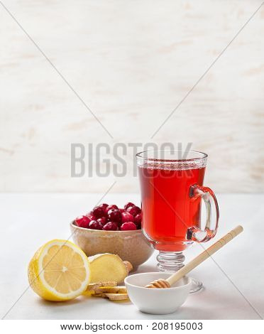 cranberries lemon ginger drink in a glass cup cranberries in a bowl half a lemon slices of ginger on a white background