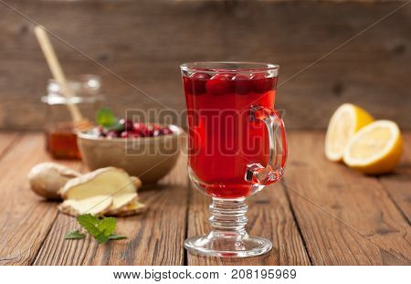 cranberries lemon ginger drink in a glass beaker cranberries in a bowl half a lemon slices of ginger on an old wooden background