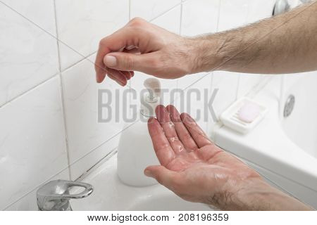Close up of a man washing hands using liquid soap. Focus on the top of the liquid soap bottle