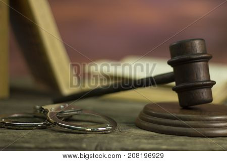 Judges Gavel and handcuffs on rustic table.