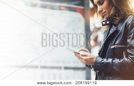 Girl in leather jacket holding smart phone on background map light box in sun atmospheric city hipster using in female hands and texting mobile glitter street lifestyle tourist planing route in summer concept