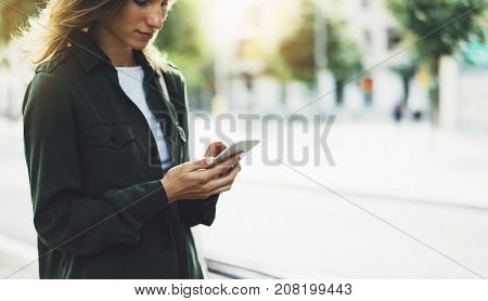 Girl holding smart phone on background sun atmospheric city and bike hipster using in female hands and texting mobile street lifestyle and flare sun tourist planing route in summer gadget concept