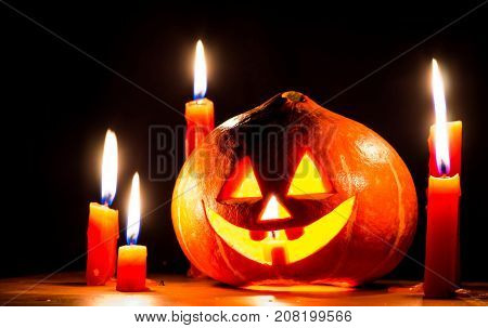 spooky halloween pumpkin with candles on black background