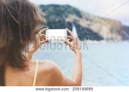 Hipster girl photograph on smart phone gadget in sand coastline mock up of blank screen. Traveler hold and using in female hand mobile on background seascape horizon. Tourist and blue sun ocean lifestyle