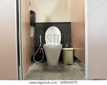toilet door opening and white flush toilet with a trash cans and box of toilet paper.