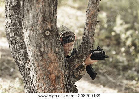 Child in camouflage with a gun shoots laser tag in the forest. Lasertag shooting game toned
