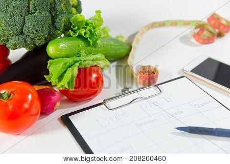 Vegetables measuring tape mobile phone and notebook with diet plan isolated on white background top view. Nutritionist doctor workspace concept