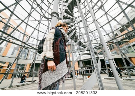 a girl in unusual clothes is standing inside a beautiful building