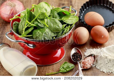 Fresh spinach in red colander and ingredients to cook spinach quiche