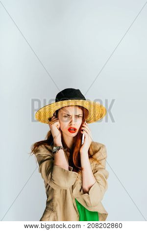 A girl in a straw hat is talking on the phone and looks angry