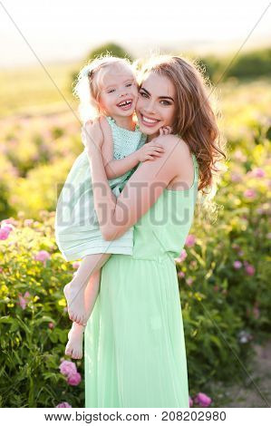 Smiling kid girl 3-4 year old on mothers hands wearing similar dresses standing in meadow. Looking at camera. Motherhood. Summer season. 20s.