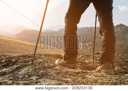 hipster in a cap and a red jacket with sticks for Nordic walking with a backpack and a folded rug for relaxation stands in the mountains against the backdrop of rocks and distant Caucasian lands.