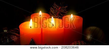 Christmas background with four red advent candles and golden decoration.