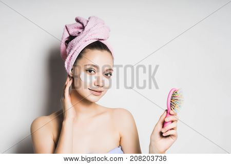 girl with a towel on her head smiling put on face mask with a check in hands