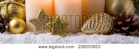 Christmas background with white advent candles and golden decoration.